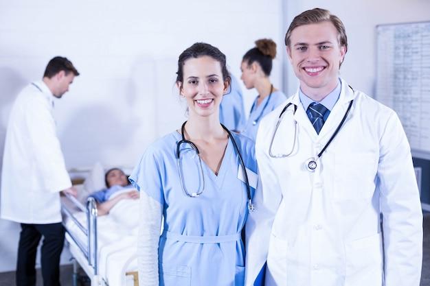 Portret van artsen het glimlachen en andere arts die een patiënt in het ziekenhuis onderzoeken