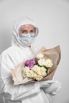 Portret van artsenvrouw in beschermend kostuum, masker, glazen en handschoenen met boeket bloemen.