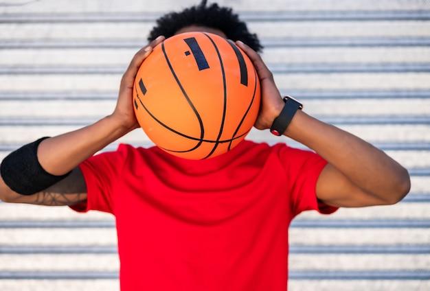 Portret van atleet man die een basketbalbal houdt terwijl hij buiten staat