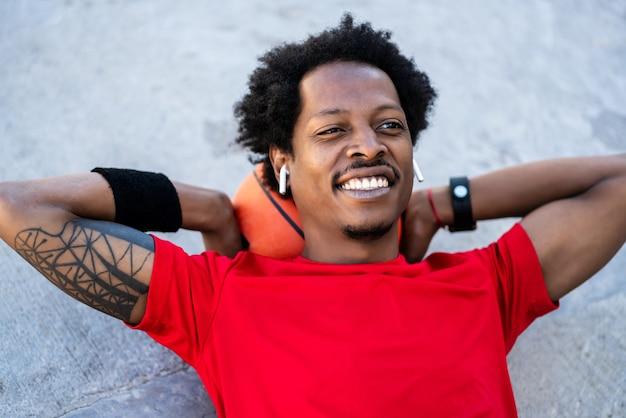 Portret van atleet man ontspannen en tot op de vloer na training buitenshuis