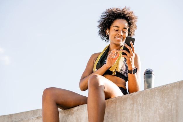 Portret van atleet vrouw met behulp van haar mobiele telefoon en ontspannen na de training buitenshuis.