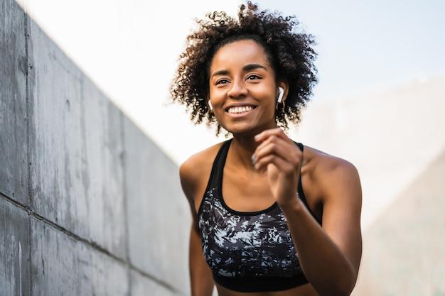 Portret van atleet vrouw uitgevoerd en oefening buitenshuis.