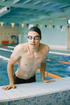 Portret van atleet zwemmer in een pet aan de zijkant in het zwembad. zwemmer in binnenzwembad die uit het water komt.
