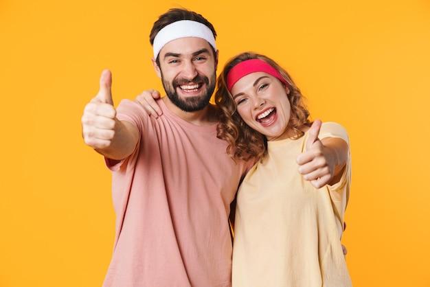 Portret van atletisch jong koppel met hoofdbanden glimlachend en gebaren duimen omhoog geïsoleerd op geel