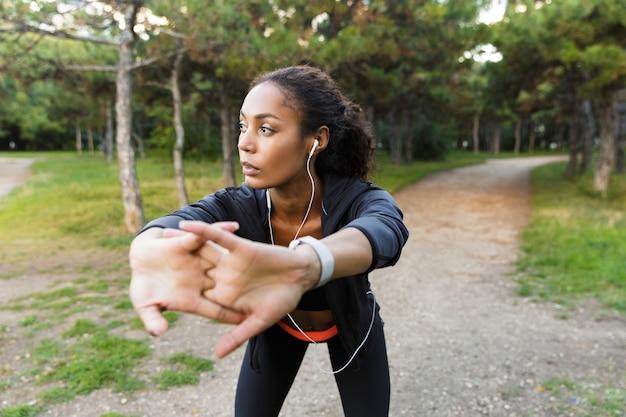 Portret van atletische afro-amerikaanse vrouw 20s dragen zwarte trainingspak doen oefeningen, en haar lichaam uitrekken in groen park