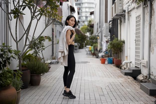 Portret van atletische aziatische vrouw die buiten in de stad poseert