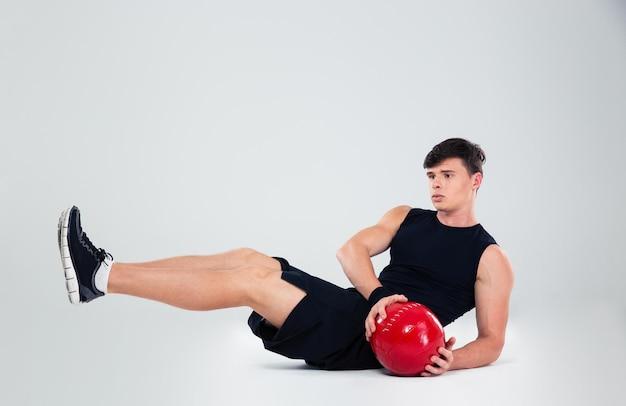Portret van atletische man training met fitness bal geïsoleerd
