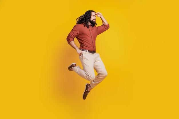 Portret van avontuurlijke nieuwsgierige kerel sprong handen voorhoofd kijken lege ruimte op gele achtergrond