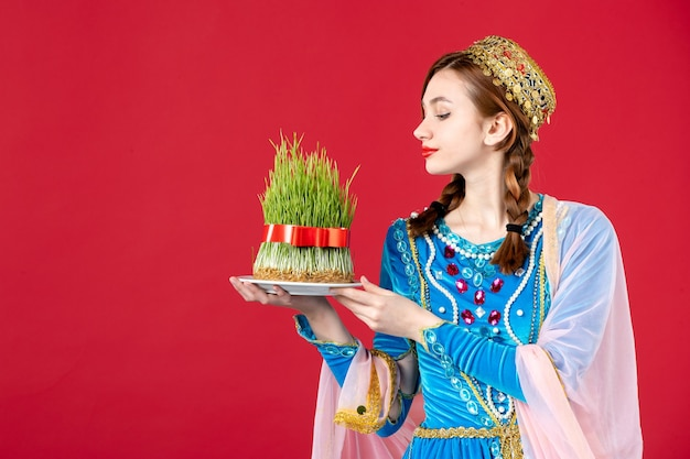 Portret van azeri vrouw in traditionele kleding met semeni op rood