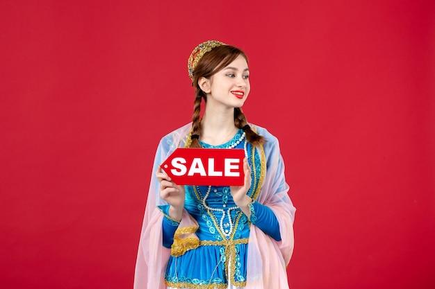 Portret van azeri-vrouw in traditionele kleding met verkoopnaambordje op rood