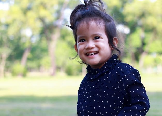 Portret van aziatisch gelukkig meisje dat gelukkig in het park glimlacht