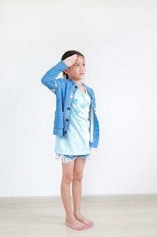 Portret van aziatisch klein kind die met hand bij voorhoofd groeten