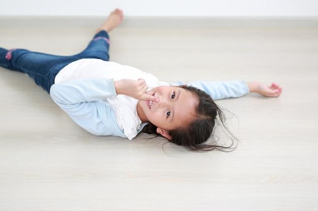 Portret van aziatisch klein kind met wijsvinger op neus die op houten laminaatvloer liggen