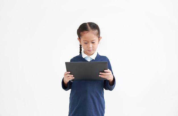 Portret van aziatisch klein kindmeisje in schooluniform met behulp van tablet geïsoleerd op wit