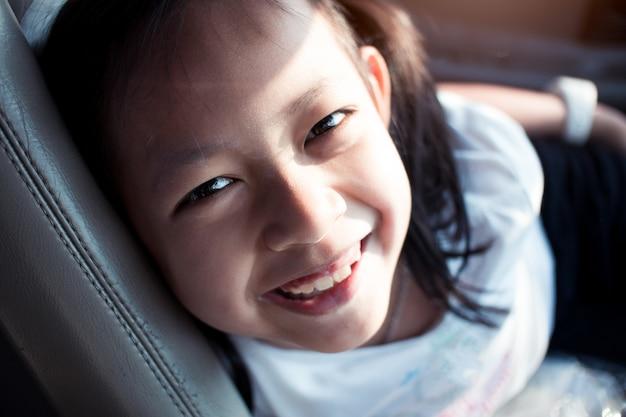 Portret van aziatisch meisje dat in de auto glimlacht