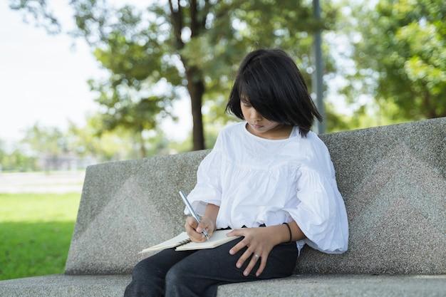 Portret van aziatisch meisje die in agenda in het groene park schrijven openlucht