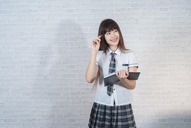 Portret van aziatisch meisje op witte muurachtergrond