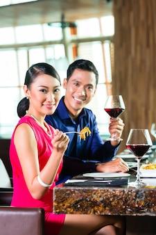 Portret van aziatisch paar dat in restaurant eet