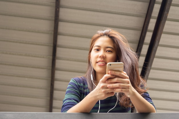 Portret van aziatische 20s tiener vrouw luisteren naar muziek met oortelefoon.