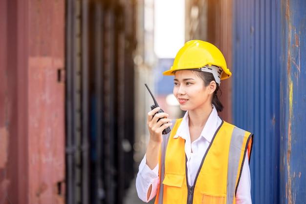 Portret van aziatische arbeidersvrouw in veiligheidsuniform die met walkietalkie spreekt