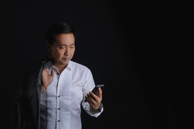 Portret van aziatische bedrijfsmens die telefoon bekijkt die wit overhemd draagt en nadenkend kijkt terwijl hij op donkere achtergrond staat.