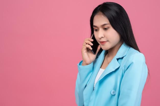Portret van aziatische bedrijfsvrouw die mobiele telefoon op roze met behulp van