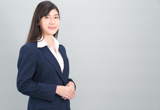 Portret van aziatische bedrijfsvrouw status geïsoleerd op grijze achtergrond