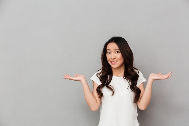 Portret van aziatische besluiteloze vrouw met donker krullend haar schouderophalend en handen opzij gooien met clueless, geïsoleerd over grijze muur