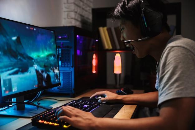 Portret van aziatische boze gamerjongen die videospelletjes op computer in donkere ruimte speelt, hoofdtelefoons draagt en met achtergrondverlichting kleurrijk toetsenbord gebruikt