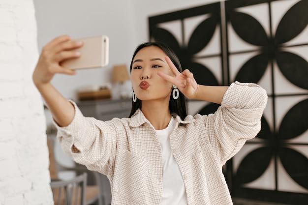 Portret van aziatische brunette vrouw in beige jas neemt selfie in gezellige kamer
