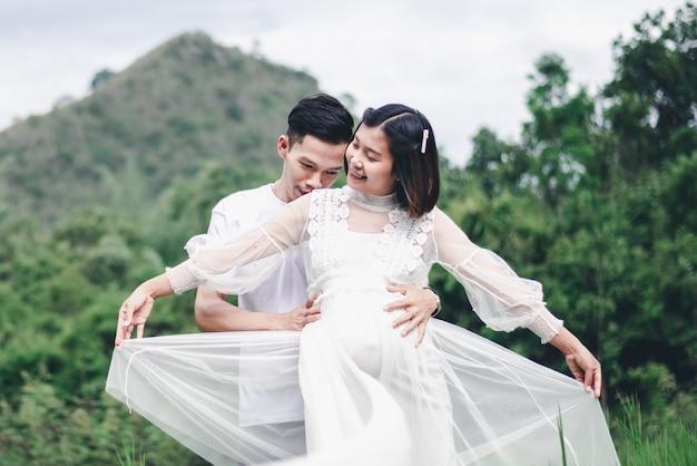 Portret van aziatische echtgenootomhelzing en het kussen van zijn zwangere vrouw met natuurlijke achtergrond