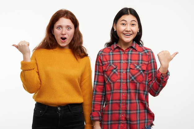 Portret van aziatische en kaukasische vrienden. gele trui en geruit overhemd dragen. kijken verbaasd en verschillende richtingen wijzend op kopie ruimte, geïsoleerd over witte muur