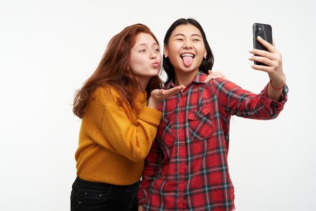 Portret van aziatische en kaukasische vrienden. gele trui en geruit overhemd dragen. luchtkus verzenden en tong tonen, selfie maken op smartphone. tribune geïsoleerd over witte muur