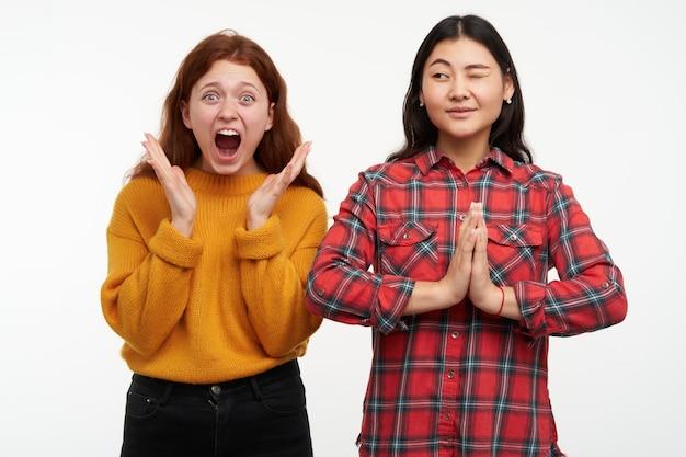 Portret van aziatische en kaukasische vrienden. mensen en levensstijlconcept. meisje probeert te mediteren terwijl haar vriend schreeuwt. een casual outfit dragen. geïsoleerd over witte muur