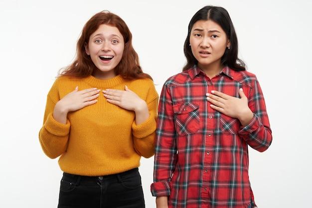 Portret van aziatische en kaukasische vrienden. wijzend op zichzelf, hebben verschillende gevoelens. gele trui en geruit overhemd dragen. geïsoleerd over witte muur