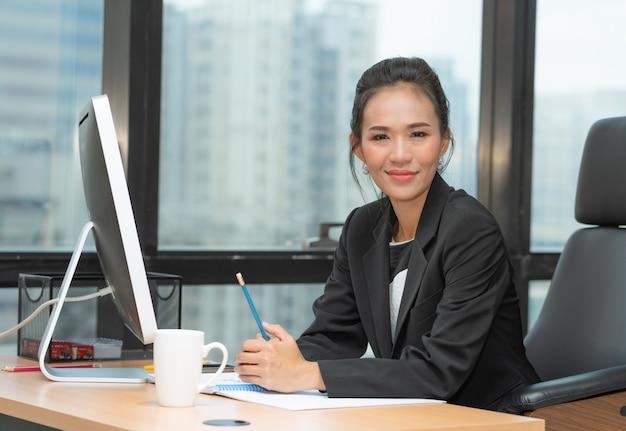 Portret van aziatische hogere bedrijfsvrouwenzitting op haar bureau die met computer op het kantoor werken