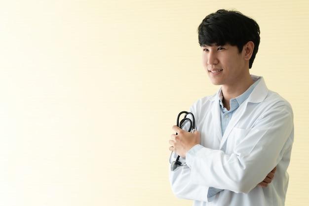 Portret van aziatische jonge arts met gekruiste holdingsstethoscoop in het ziekenhuis