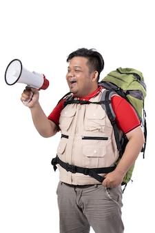 Portret van aziatische jonge backpacker die met megafoon gilt