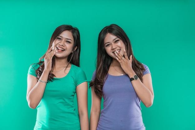 Portret van aziatische jonge meisjestweelingen lachen terwijl het bedekken van hun mond met hun handen geïsoleerd op een groene achtergrond