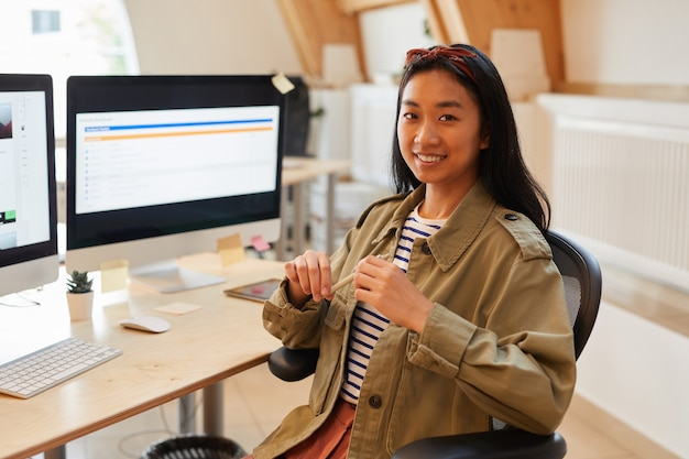 Portret van aziatische jonge ontwerper zittend op een stoel voor haar werkplek met computers en glimlachend in de camera