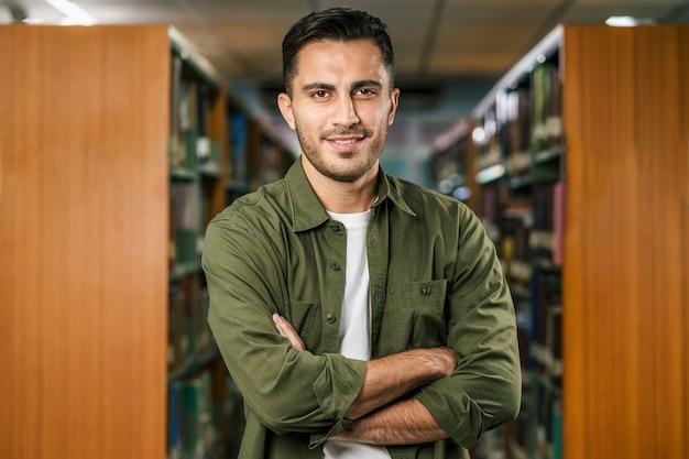 Portret van aziatische jonge student in casual pak in bibliotheek van universiteit of hogeschool over boekenplank, leren en onderwijs, terug naar school en universitair concept