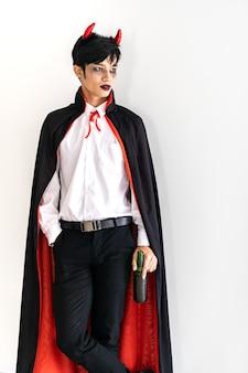 Portret van aziatische jonge volwassen tienermens die halloween-kostuumdoek dragen