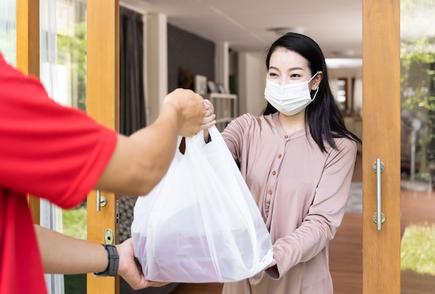 Portret van aziatische jonge vrouw die gezichtsmasker draagt dat pakket ontvangt van handen bezorger bij de deur tijdens coronavirus of covid-19-uitbraak of hypochondrie