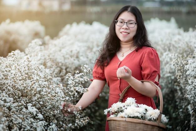 Portret van aziatische jonge vrouw gelukkige reiziger met rode jurk genieten in witte bloei of white marguerite daisy bloemenveld om een bloemenmand te houden in de natuurtuin van in chiang mai, thailand