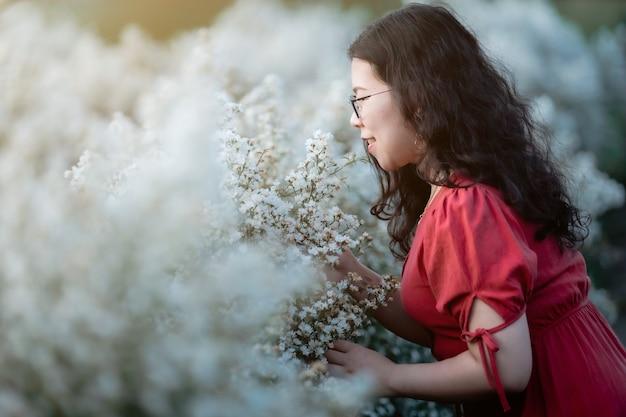Portret van aziatische jonge vrouw gelukkige reiziger met rode jurk genieten in witte bloei of witte margarita bloemenveld in de natuurtuin van in chiang mai, thailand, reizen ontspannen vakantie concept
