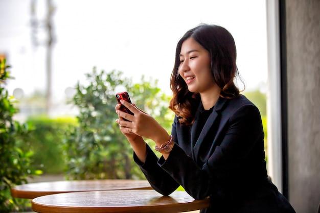 Portret van aziatische jonge vrouw lachend kijken naar telefoon