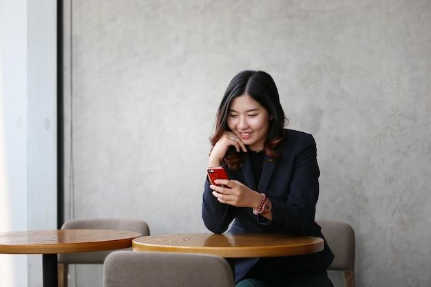 Portret van aziatische jonge vrouw lachend kijkt naar mobiele telefoon