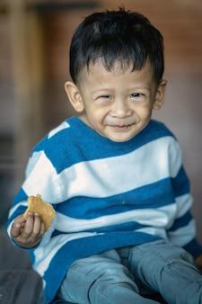 Portret van aziatische jongen die het koekje in huis, familieconcept eet