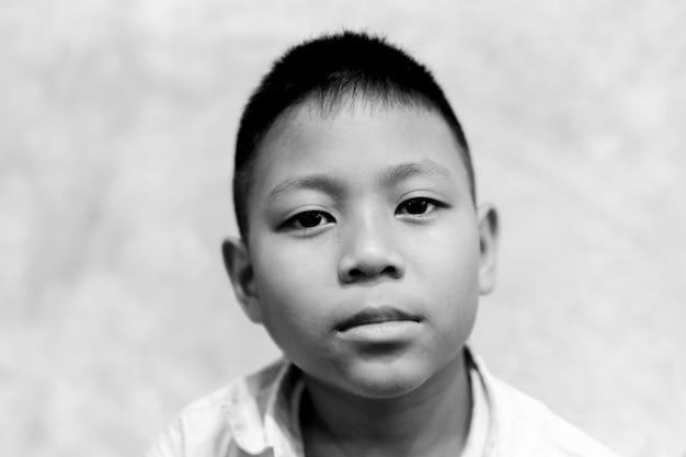 Portret van aziatische jongen die met scheur op zijn gezicht in zwart-wit schreeuwt.