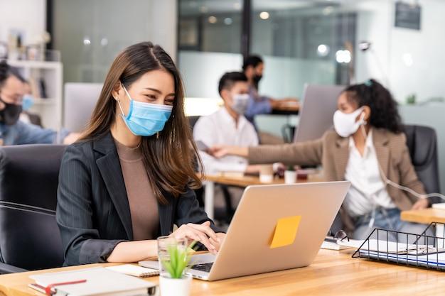 Portret van aziatische kantoor werknemer zakenvrouw dragen beschermend gezichtsmasker werk in nieuw normaal kantoor